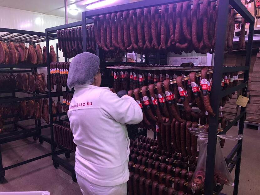 A worker labels sausages in a meat processing factory in Hungary