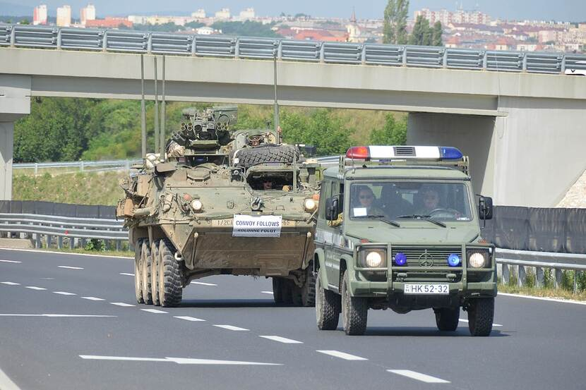A military convoy travels on a highway.
