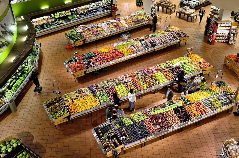 Picture of people buying fruits and vegetables at a supermarket.