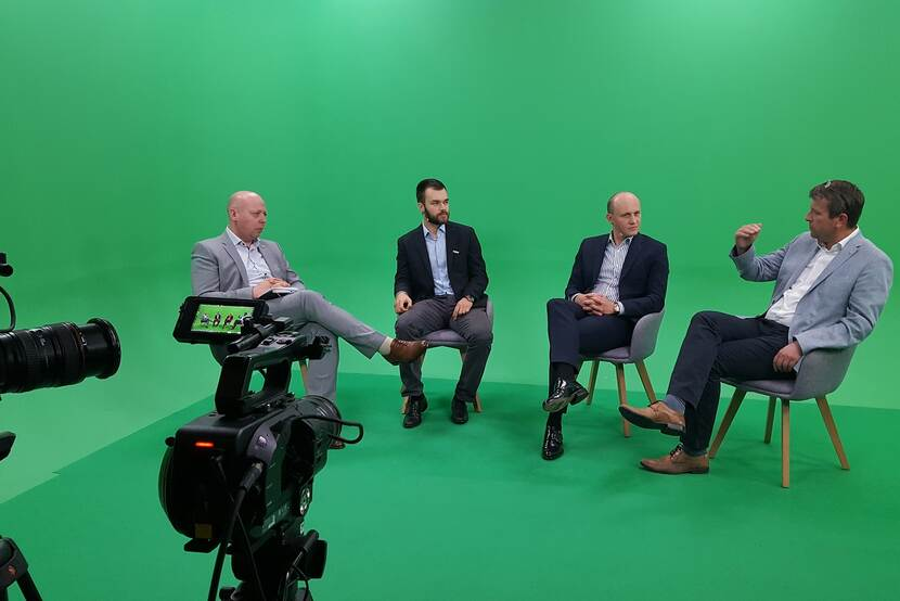 panel discussion in a green box with visible camera's