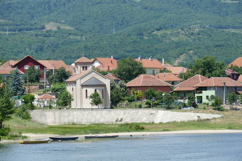 Houses and a temple can be seen in a village on the banks of the River Danube in Serbia.