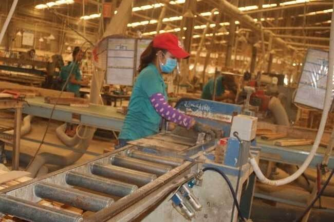 Workers process wooden products at a local factory.